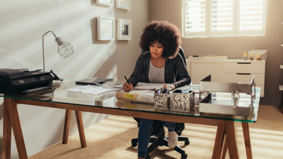 African woman working on new building plans while sitting at her desk. Female interior designer working at home office.